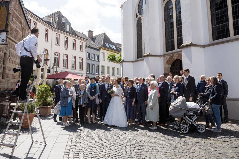 Hochzeitsfotograf fotografiert Gruppe an einer Kirche in Xanten